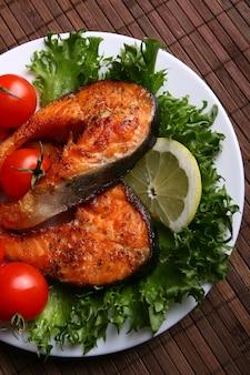 調理されたサーモンステーキ、ハーブ、レモン、ニンニク、オリーブオイル、トマト