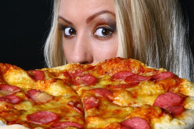 Красивая молодая женщина ест пиццу