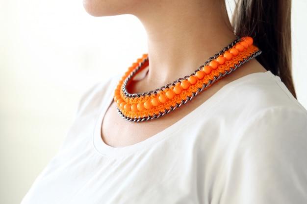 オレンジ色のネックレスを着ている少女