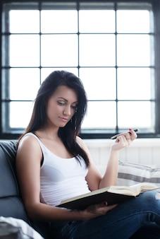 Красивая девушка учится с книгой