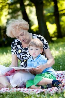 Бабушка читает книгу своему внуку