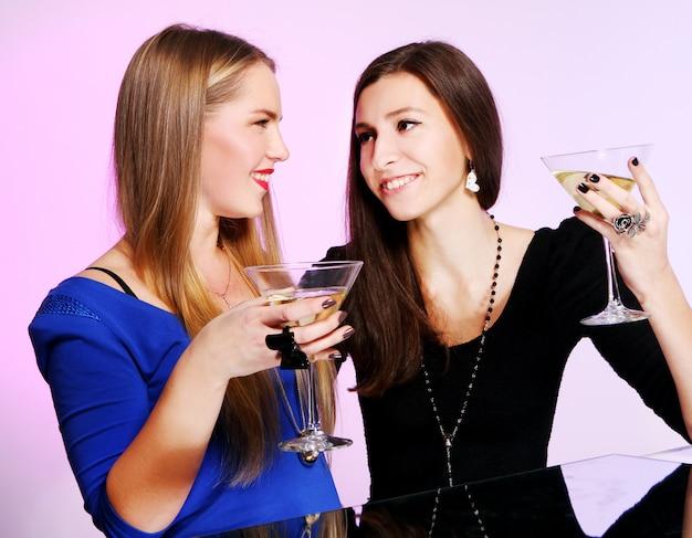 Две веселые подружки с разноцветными коктейлями