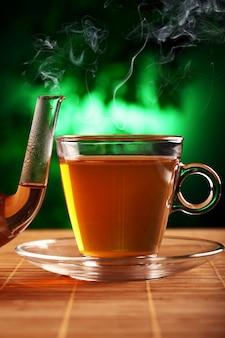 Горячий зеленый чай в стеклянном чайнике и чашке