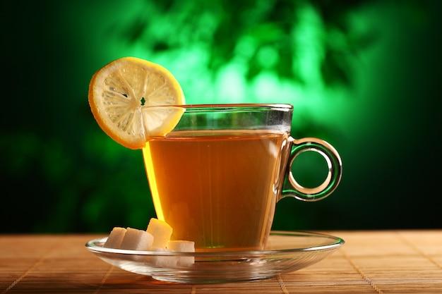 Чашка горячего зеленого чая с сахаром и лимоном