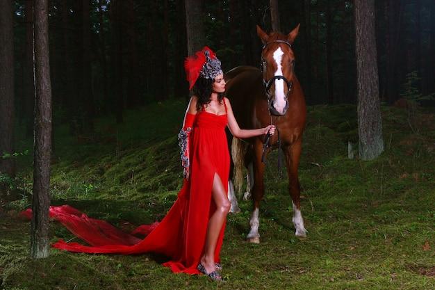 Красивая женщина с коричневой лошадью