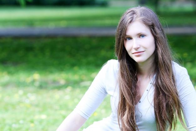Красивая женщина, сидящая на траве
