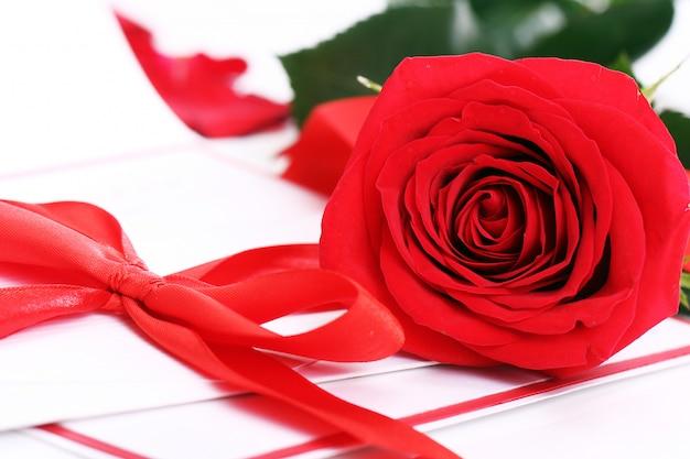 Красная роза и праздничный конверт