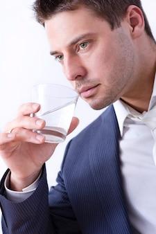 水のガラスを持ったビジネスマン