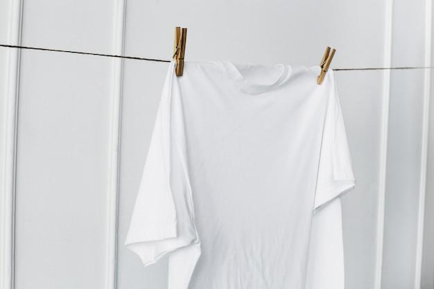 壁にぶら下がっている白いシャツ