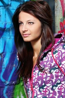 落書きの壁に若い女性
