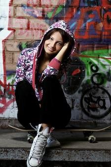 スケートボードの上に座っている若い女性