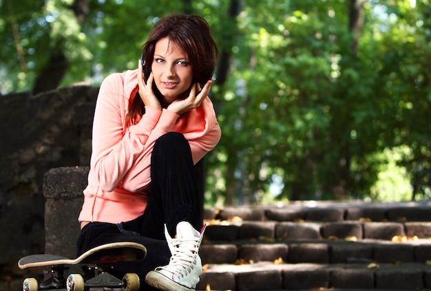 Красивая девушка подросток с наушниками в парке