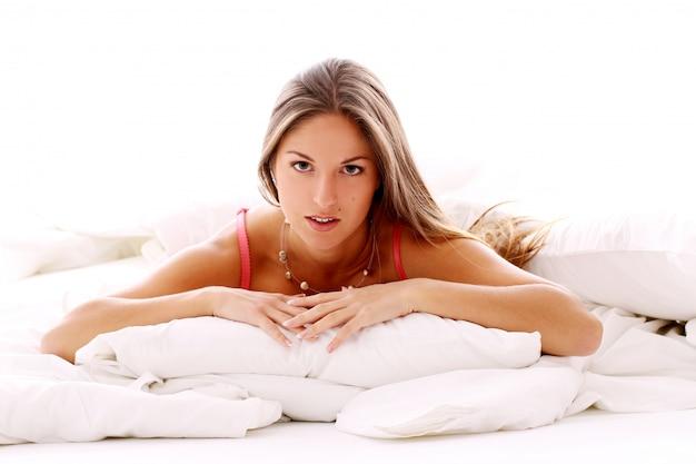 Молодая женщина, отдыхая в постели на утро