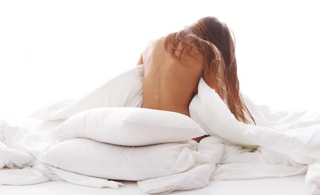 朝はベッドでリラックスした若い女性