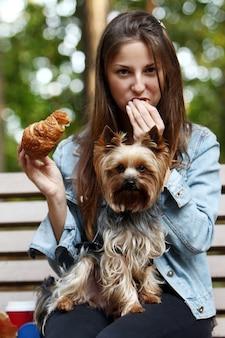 Женщина обедает во время прогулки с собакой