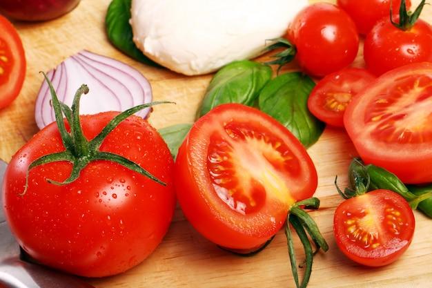 トマト、バジル、モッツァレラチーズの木の板