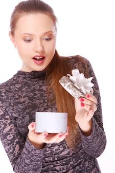 手に小さなギフトボックスを持つ若い女性