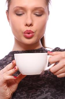 ホットコーヒーのカップを持つ若い女