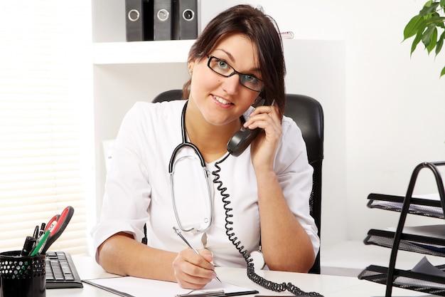Доктор молодой женщины говоря по телефону