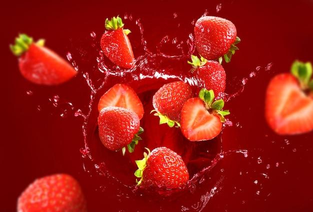 たくさんのジュースに落ちるイチゴ