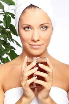 熱いお茶のカップを持つ若い女