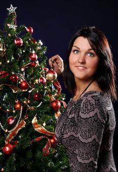 Женщина украшают елку