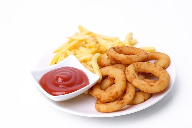 Луковые кольца и картофель фри на тарелке