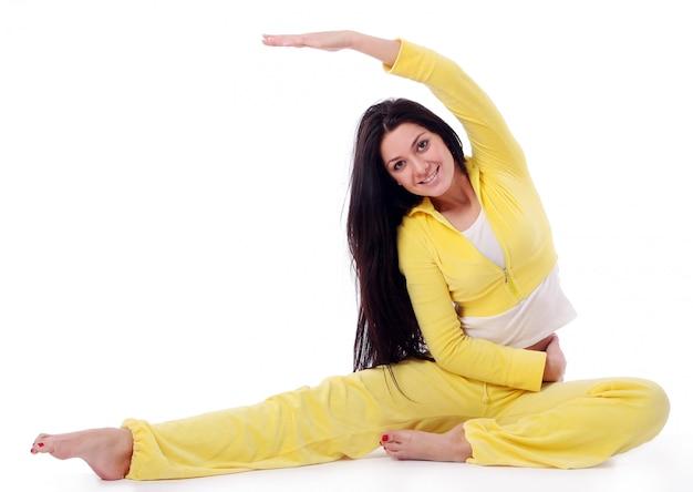 Улыбающаяся молодая девушка делает упражнения