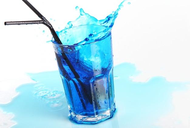白で隔離される水しぶきと青いカクテル
