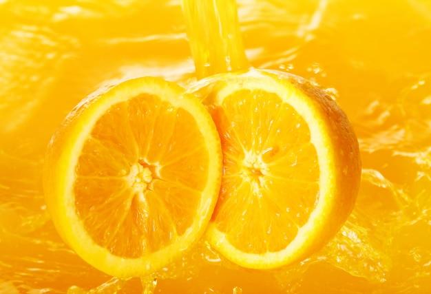 Свежие апельсины падают в сок