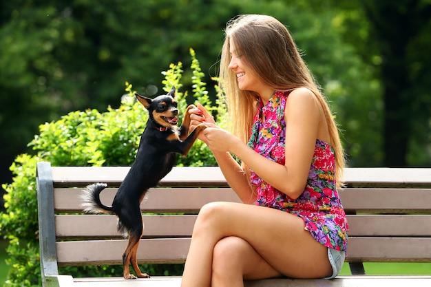 Молодая и счастливая девушка со своей милой собакой
