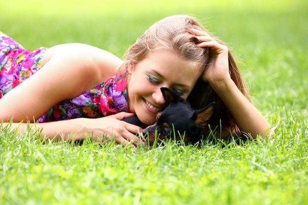 Счастливая женщина, лежа на траве со своей собакой