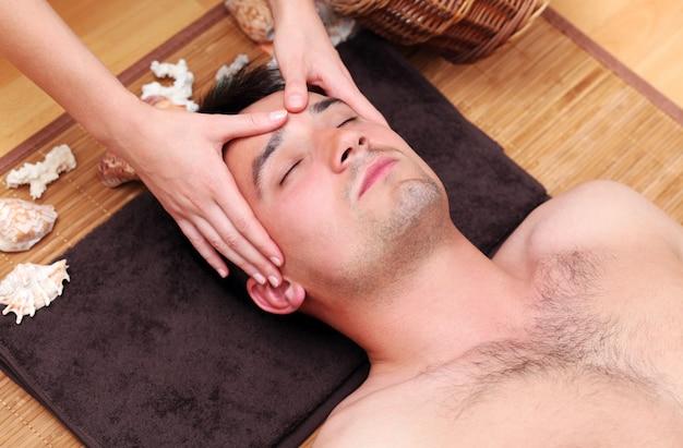 Мужчина наслаждается массажем лица