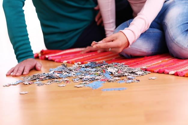 Пара делает головоломку на полу