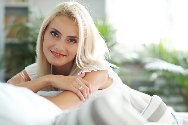 Белокурая женщина отдыхает на диване у себя дома