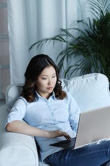 Красивая азиатская женщина дома с компьтер-книжкой