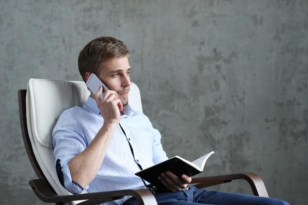 スマートフォンとノートを持つハンサムな男