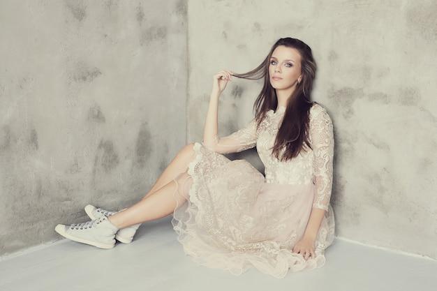 Прекрасная женщина позирует с элегантным белым платьем