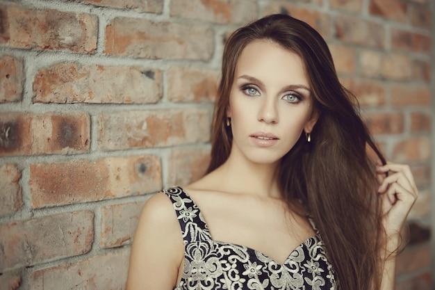 素敵な女性がエレガントな黒のドレス、ファッションのコンセプトでポーズ