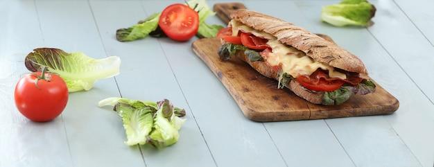 木の板テーブルに野菜と大きなビーガンサンドイッチ