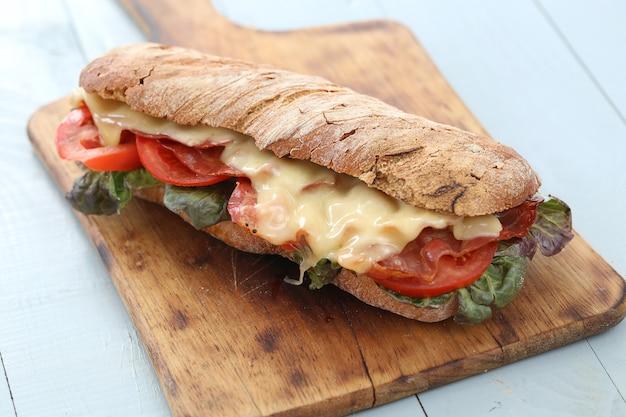 Большой веганский бутерброд с овощами на столе деревянная доска
