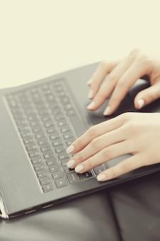 ノートパソコンのキーボード上の指で女性の手