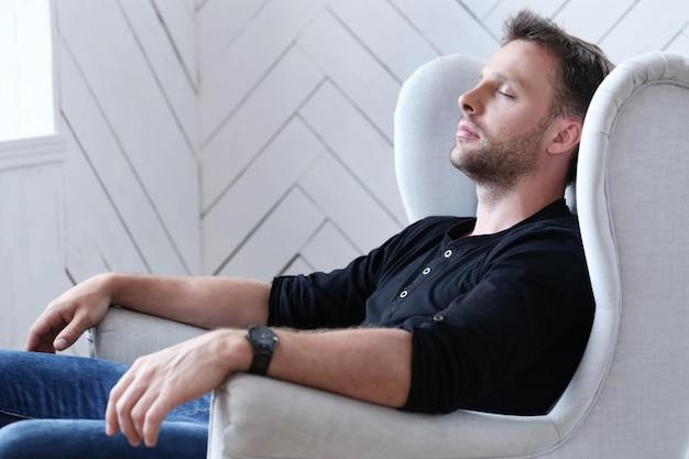 肘掛け椅子で寝ているハンサムな男