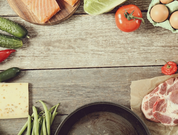 Пустая сковорода и овощи кадр фон, вид сверху
