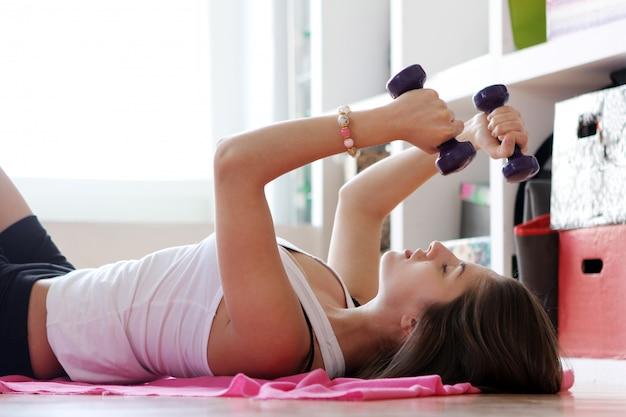 Молодая женщина делает гимнастические упражнения