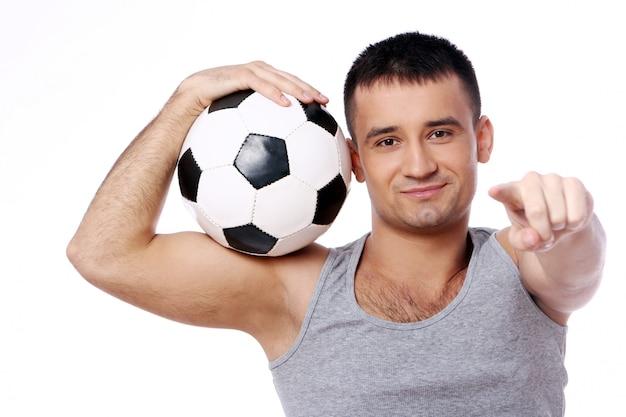 Привлекательный парень держит футбольный мяч