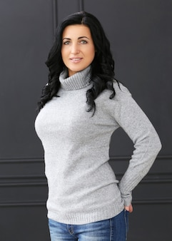Красивая женщина с серым свитером и джинсами