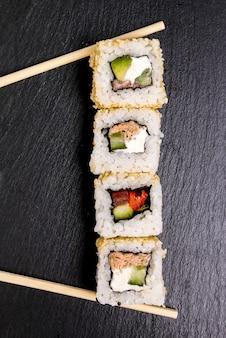 Вкусные суши на черной тарелке