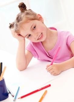 Милая маленькая девочка, рисование красочными карандашами