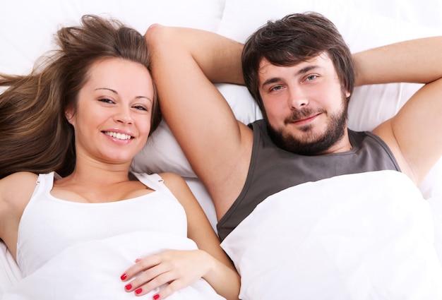 笑顔のカップルがベッドでリラックス